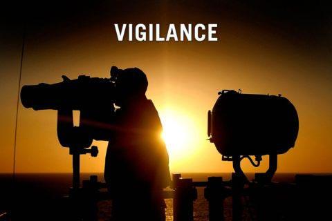 man with binoculars back lit by spotlight